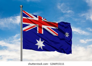 Flag of Heard Island and McDonald Islands waving in the wind against white cloudy blue sky.