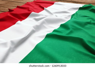 Flag of Hungary on a wooden desk background. Silk Hungarian flag top view.