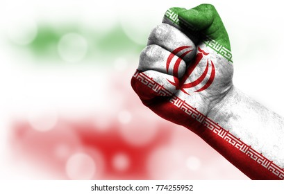 Flag of Iran painted on male fist, concept of conflict