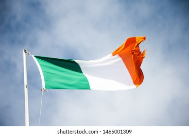 The flag of Ireland waves in the wind from behind a boat.