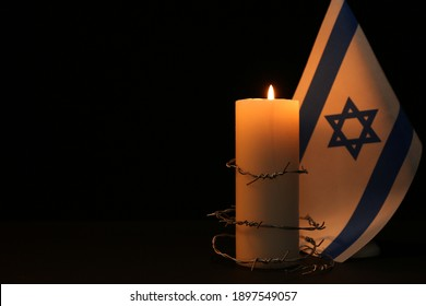 Flag of Israel, barbed wire and burning candle on black background, space for text. Holocaust memory day