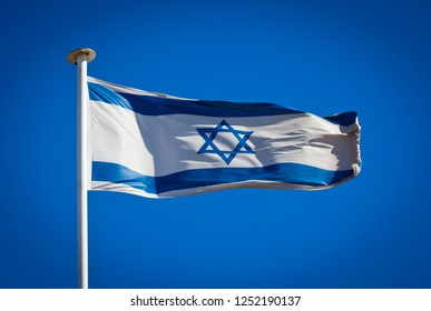 Flag of Israel blowing in strong wind against pure blue sky. Showing star of david hexagram, symbol of national patriotism.