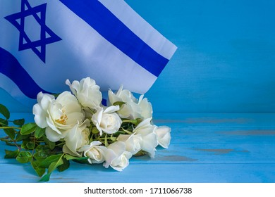 Flag of Israel and bouquet of white flowers on blue wooden background with copy space. Independence Day celebration.