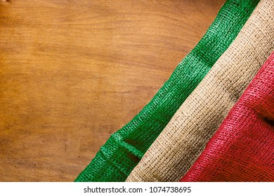 Flag of Italy from coarse canvas fabric is built on a wooden surface
