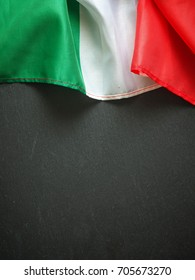 Flag of Italy on a dark slate texture, using as menu or travel background with space for text or image