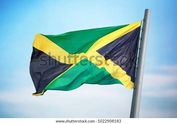 Flag of Jamaica flying against a blue sky