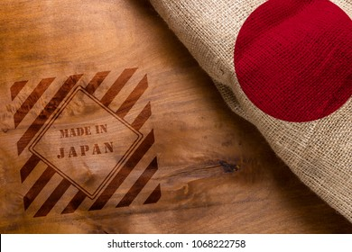 A flag of Japan made from rough fabric on a wooden background. Stamp Made in Japan
