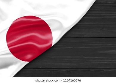 Flag of Japan and place for text on a dark wooden background