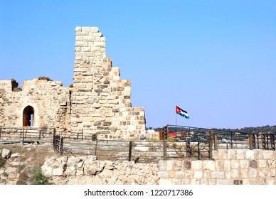 Flag of Jordan and stone wall in medieval crusaders castle, Al Karak, Jordan, Middle East