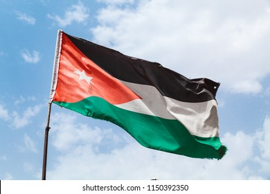 Flag of Jordan waving on wind over cloudy sky