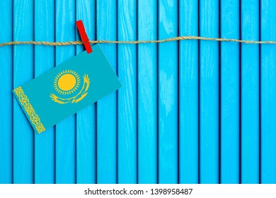 Flag of Kazakhstan hanging on clothesline attached with wooden clothespins on aqua blue wooden background. National day concept.