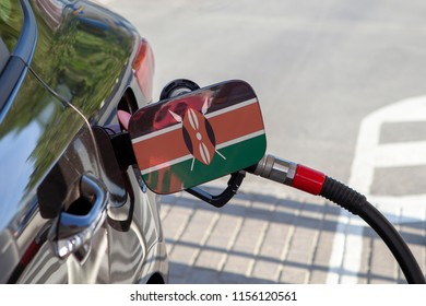 Flag of Kenya on the car's fuel tank filler flap. Fueling car with petrol pump at a gas station. Petrol station. Gasoline and oil products. Close up.