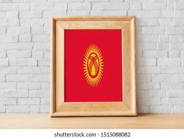 Flag of Kyrgyzstan on photo frame. Kyrgyzstan Flag in wooden frame.