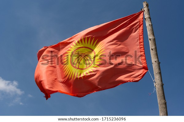 Flag of Kyrgyzstan in a valley and mountains on a summers day with blue sky.