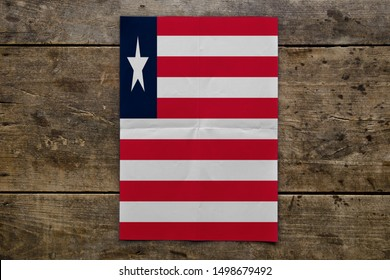 Flag of Liberia on wooden board. Paper Flag of Liberia on wooden table.