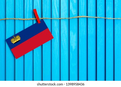 Flag of Liechtenstein hanging on clothesline attached with wooden clothespins on aqua blue wooden background. National day concept.