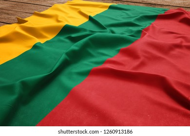 Flag of Lithuania on a wooden desk background. Silk Lithuanian flag top view.
