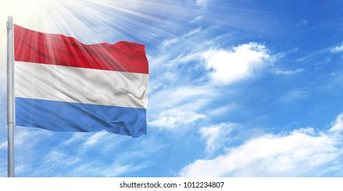 Flag of Luxembourg on flagpole against the blue sky
