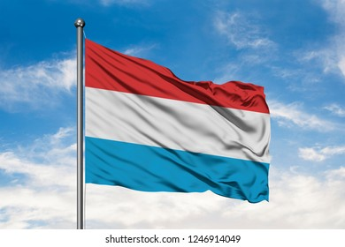 Flag of Luxembourg waving in the wind against white cloudy blue sky.