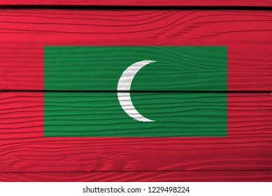 Flag of Maldives on wooden wall background. Grunge Maldives flag texture, green with red border and white crescent on center.