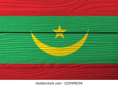 Flag of Mauritania on wooden wall background. Grunge Mauritania flag texture, Two red stripes flanking a green field with a golden crescent and star.