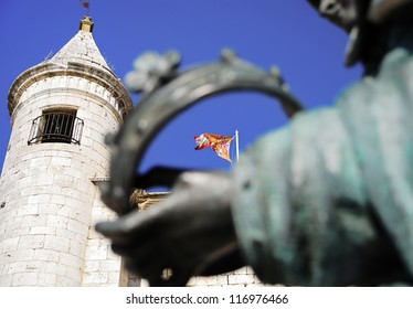 Flag and medieval tower silhouetted against the blue sky.