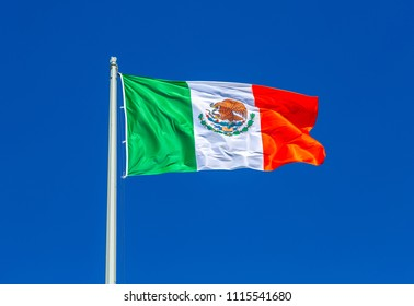 Flag of Mexico flying in the wind against the blue sky