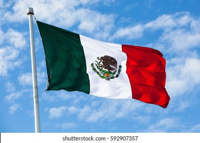 Flag of Mexico waving in the wind, over partly cloudy sky