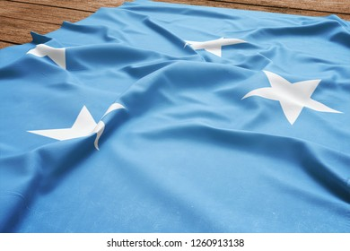 Flag of Micronesia on a wooden desk background. Silk Micronesian flag top view.