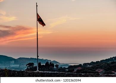 Flag of Montenegro on the background of the sunset. Little light. Bar, Montenegro.