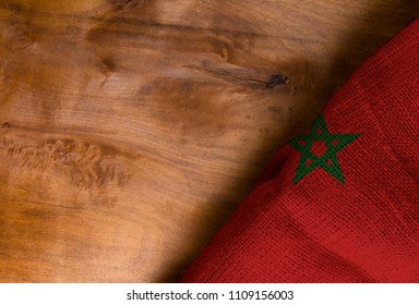 Flag of Morocco from rough fabric on a wooden surface