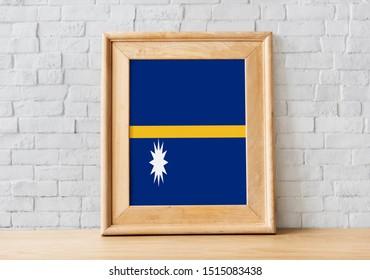 Flag of Nauru on photo frame. Nauru Flag in wooden frame.
