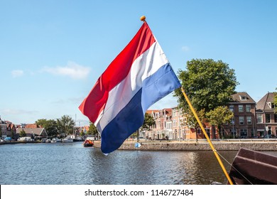 flag of Netherlands against the backdrop of the river in Haarlem