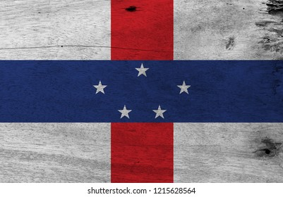 Flag of Netherlands Antilles on wooden plate background. Grunge Netherlands Antilles flag texture, white with vertical red and horizontal blue and five white stars.