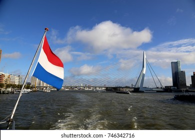 Flag of the Netherlands flying on boat with view of Rotterdam harbor and Erasmusbrug (Erasmus Bridge)