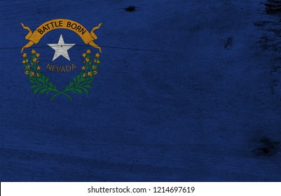 Flag of Nevada on wooden plate background. Grunge Nevada flag texture, The states of America. Solid cobalt blue field. The canton contains two sagebrush branches encircling a silver star.