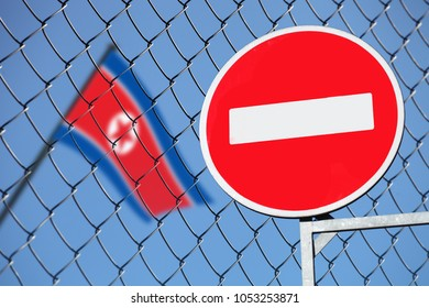 the flag of North Korea behind a metal fence. with a stop sign