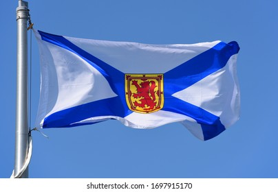 Flag of Nova Scotia province on blue sky. Photo taken in Grand Pre in Nova Scotia, Canada.