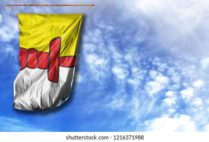 Flag of Nunavut. Vertical flag, against blue sky with place for your text