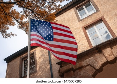 Аmerican flag on autumn background. Thanksgiving day. Freedom and Democracy symbols. Beautiful American flag waving on the background of an old building. Fall season.