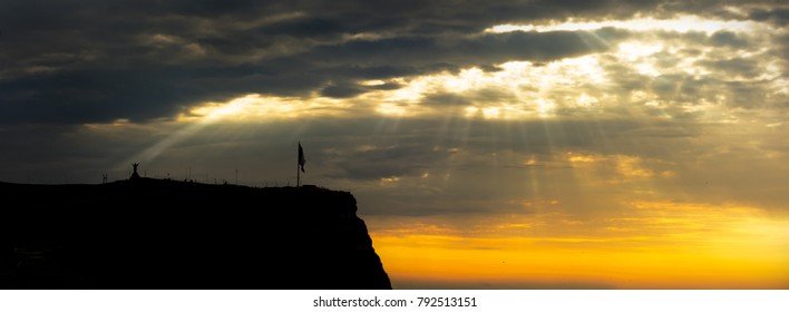 flag on the top of a mountain with a divine light with rays of light illuminating Christ