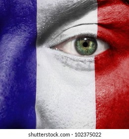Flag painted on face with green eye to show France support in sport matches