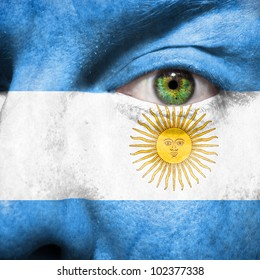 Flag painted on face with green eye to show argentina support