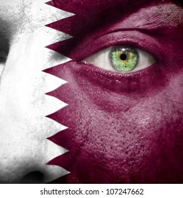 Flag painted on face with green eye to show Qatar support