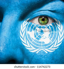 Flag painted on face with green eye to show United Nations support
