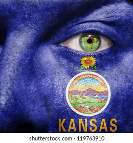 Flag painted on face with green eye to show Kansas support