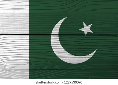 Flag of Pakistan on wooden wall background. Grunge Pakistani flag texture, a white star and crescent on a dark green field, with a vertical white stripe at the hoist.