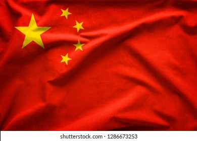 Flag of the Peoples Republic of China or Five-Starred Red Flag representing the Communist Party in a close up full frame textured view
