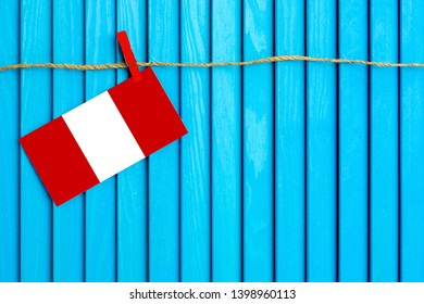 Flag of Peru hanging on clothesline attached with wooden clothespins on aqua blue wooden background. National day concept.