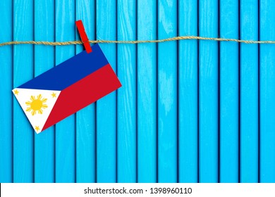 Flag of Philippines hanging on clothesline attached with wooden clothespins on aqua blue wooden background. National day concept.